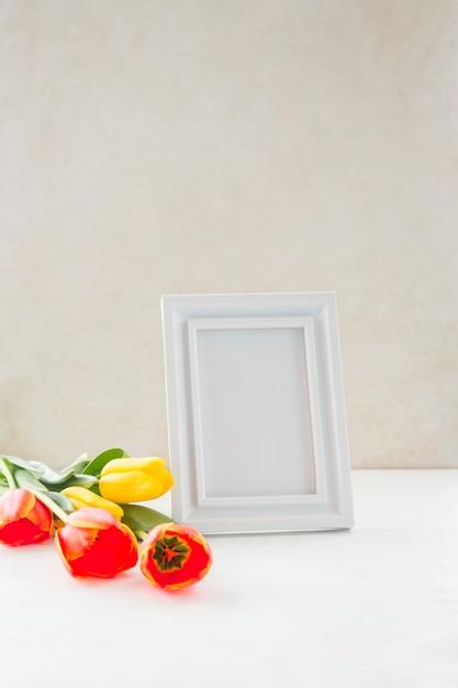 Kwiaty i pusta ramka na zdjęcia umieszczone w pobliżu ściany Darmowe Zdjęcia