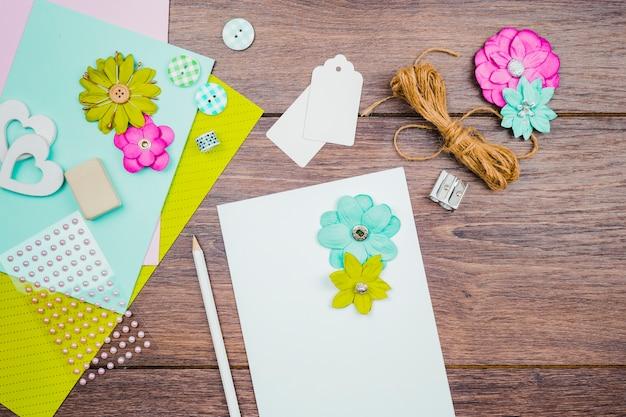 Kwiaty na białym papierze z ołówkiem; tagi; kwiat i lina na drewnianym biurku Darmowe Zdjęcia