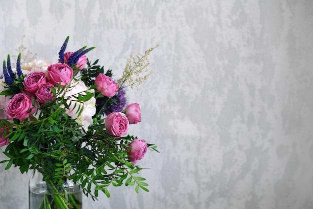 Kwiaty W Szklanym Słoju Na Szarym Tle Betonu. Vintage Wystrój Domu. Skopiuj Miejsce Na Tekst. Premium Zdjęcia