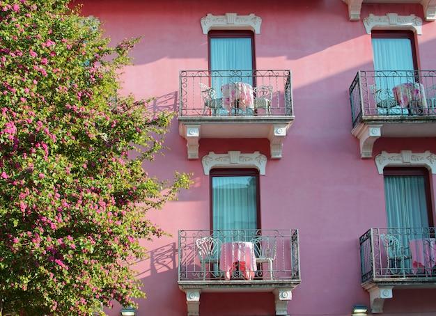 Kwitnące Drzewo I Piękny Różowy Dom Z Balkonami W Sirmione Premium Zdjęcia