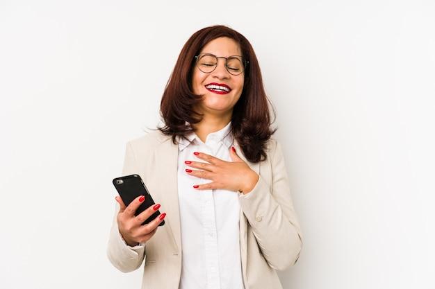 Łacińska Kobieta W średnim Wieku, Trzymając Telefon Komórkowy Na Białym Tle, Głośno Się śmieje, Trzymając Rękę Na Piersi. Premium Zdjęcia