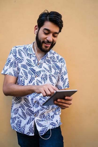 Łaciński Mężczyzna Używa Jego Cyfrowego Pastylkę Z Słuchawkami. Darmowe Zdjęcia
