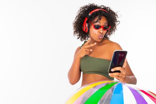 Ładna Afrykańska Kobieta W Strojach Kąpielowych Stoi Z Dużą Kolorową Gumową Piłką, Słucha Muzyki Przez Słuchawki I Robi Selfie Na Białym Tle Premium Zdjęcia