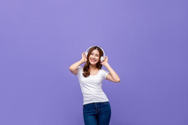 Ładna Azjatycka Kobieta Tanczy I Słucha Muzyka Na Hełmofonach Premium Zdjęcia