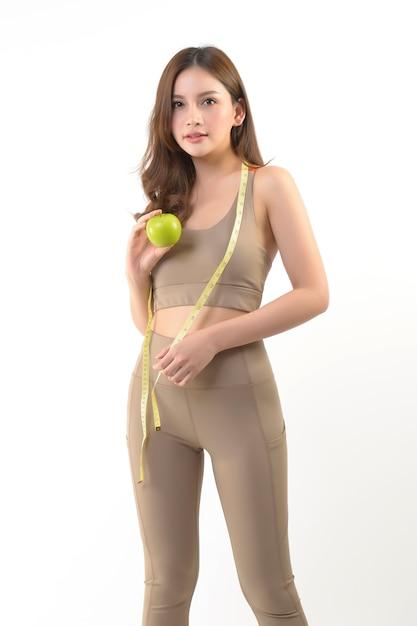 Ładna azjatykcia kobieta z jabłkiem i miarą taśmy na bielu Premium Zdjęcia