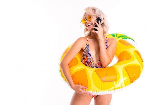 Ładna Blondynka Kaukaska Kobieta Stoi W Stroju Kąpielowym Z Gumowym Pierścieniem Plaży Ananasa, Rozmawia Przez Telefon Z Przyjaciółmi Lub Rodziną I Uśmiecha Się Na Białym Tle Premium Zdjęcia
