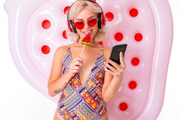 Ładna Blondynka W Stroju Kąpielowym I Okularach Przeciwsłonecznych Z Lizakiem I Telefonem W Rękach Materaca Do Pływania Słucha Muzyki Na Słuchawkach Premium Zdjęcia