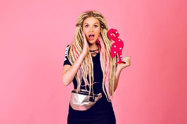 Ładna Blondynka Z Długimi Blond Dredami Trzymająca Plastikowy Flaming, Ubrana W Stylowy Sportowy, Szykowny Strój, Zaskoczona Emocjami, Pop Ostatni Styl. Darmowe Zdjęcia
