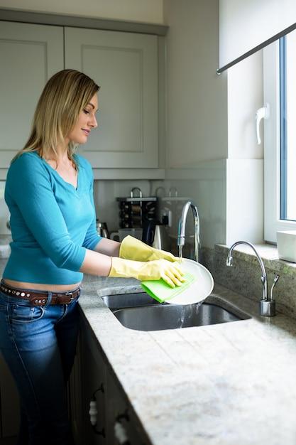 Ładna blondynki kobieta robi obowiązkom domowym Premium Zdjęcia
