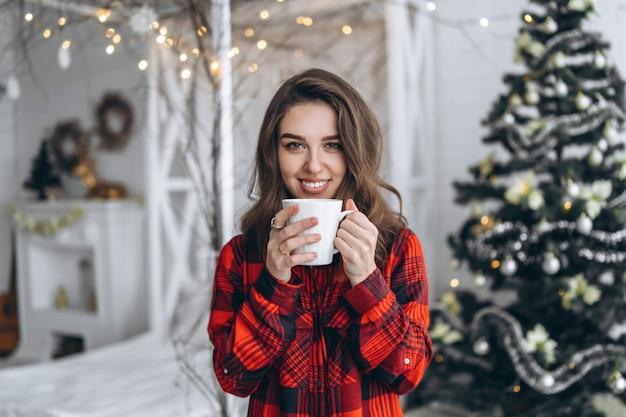 Ładna Brunetka Dziewczyna Stojąca W Pobliżu Okna, Ubrana W Czerwoną Koszulę Z Filiżanką Kawy Premium Zdjęcia