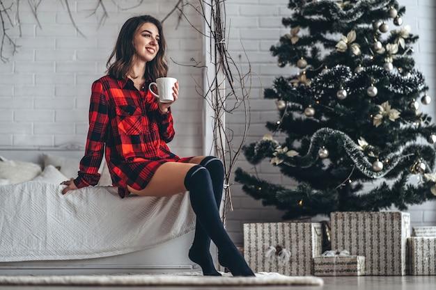 Ładna Brunetka Dziewczyna W łóżku Na Sobie Czerwoną Koszulę I Skarpetki Z Filiżanką Kawy Premium Zdjęcia