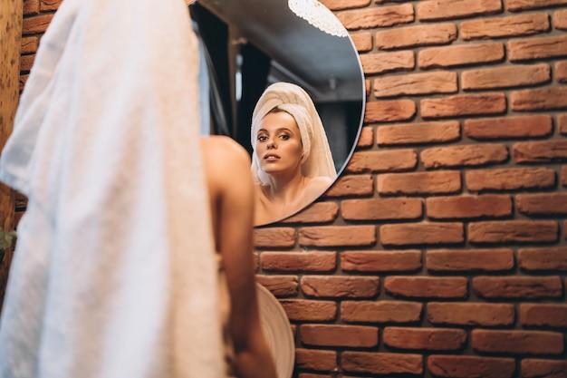Ładna Brunetka Z Ręcznikiem Stała Po Prysznicu Przy Lustrze W łazience Premium Zdjęcia