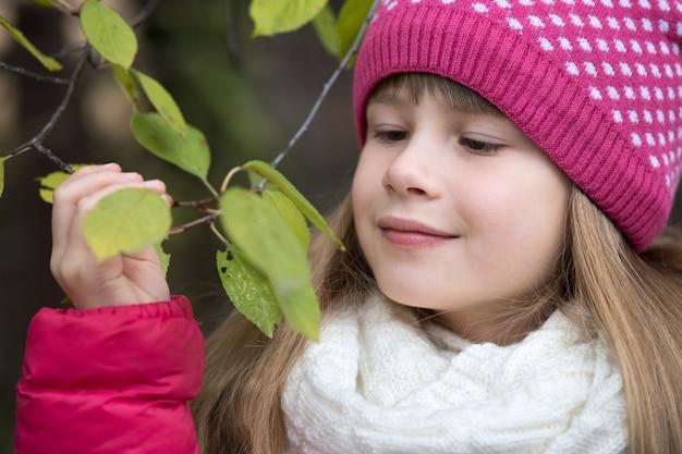Ładna Dziecko Dziewczyna Jest Ubranym Ciepłego Zimy Odzieżowego Mienie Gałąź Z Zielonymi Liśćmi W Zimnej Pogodzie Outdoors. Premium Zdjęcia