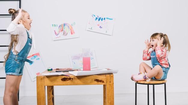 Ładna Dziewczyna Maluje Pozujący Dziewczyny Na Krześle Darmowe Zdjęcia