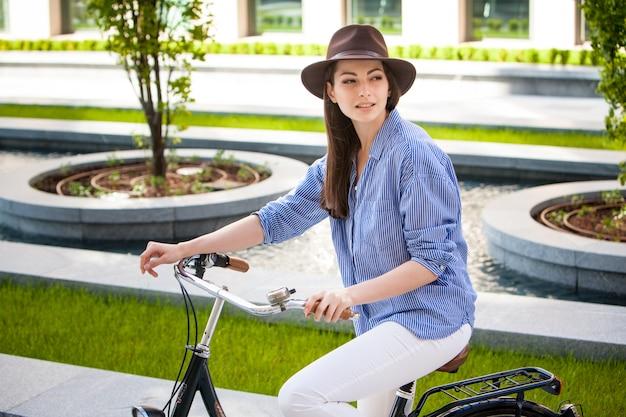 Ładna Dziewczyna W Kapeluszu Jedzie Bicykl Przy Ulicą Darmowe Zdjęcia