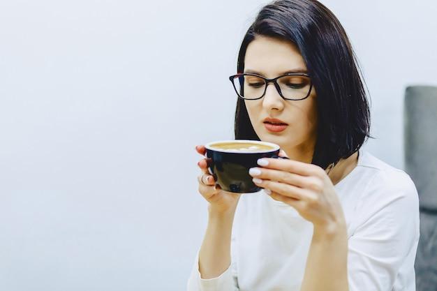 Ładna dziewczyna w kawiarni pije kawę Premium Zdjęcia