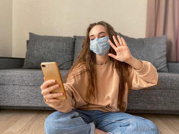 Ładna Dziewczyna W Medycznej Masce Ze Smartfonem W Rękach Rozmawia Przez łącze Wideo Z Przyjaciółmi, Krewnymi Premium Zdjęcia