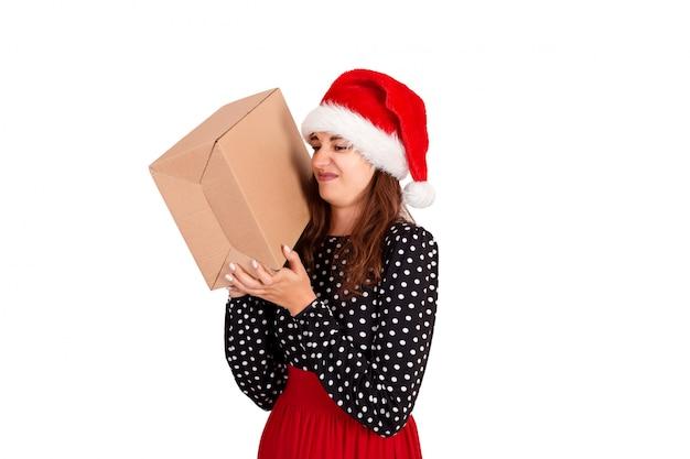 Ładna Dziewczyna W Santa Hat Nie Jest Szczęśliwa I Jest Zniesmaczona Swoim Prezentem. Odosobniony Premium Zdjęcia