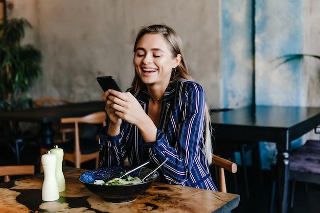 Ładna Dziewczyna Za Pomocą Telefonu Podczas Kolacji W Kawiarni. Portret Szczęśliwa Młoda Kobieta Je Warzywa. Darmowe Zdjęcia