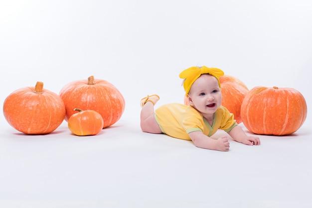 Ładna dziewczynka w żółtym ciele z żółtą kokardą na głowie Premium Zdjęcia