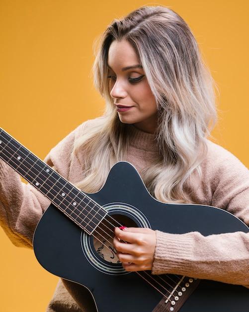Ładna kobieta gra na gitarze na żółtym tle Darmowe Zdjęcia
