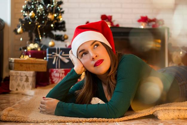 Ładna kobieta, leżąc na dywanie w salonie swojego domu z ozdób choinkowych i prezentów na drzewie. Premium Zdjęcia