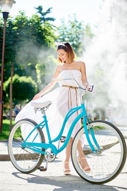 Ładna kobieta pozuje obok roweru przed fontanną Premium Zdjęcia