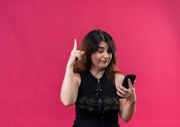 Ładna Kobieta Ubrana W Czarną Bluzkę Wskazuje, Patrząc Na Telefon Darmowe Zdjęcia