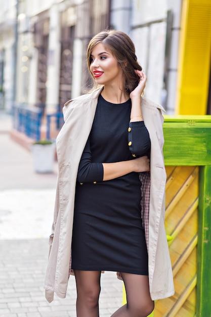 Ładna Kobieta Ubrana W Czarną Sukienkę I Beżowy Tren Ze Stylową Fryzurą I Czerwonymi Ustami Na Ulicy Darmowe Zdjęcia