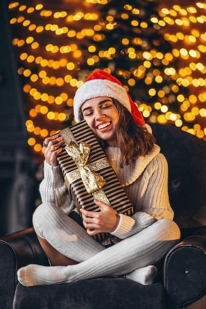 Ładna Kobieta W Ciepły Sweter, Skarpetki I świąteczny Kapelusz, Siedząc Na Krześle W Domu Z Pudełkiem Premium Zdjęcia