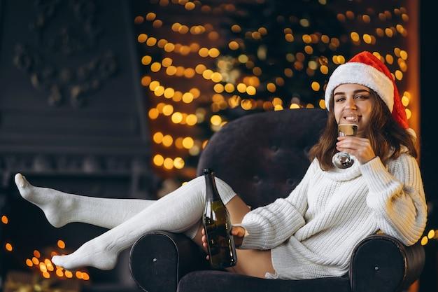 Ładna Kobieta W Ciepłym Swetrze, Skarpetkach I świątecznej Czapce, Siedząca Na Krześle Z Szampanem Premium Zdjęcia