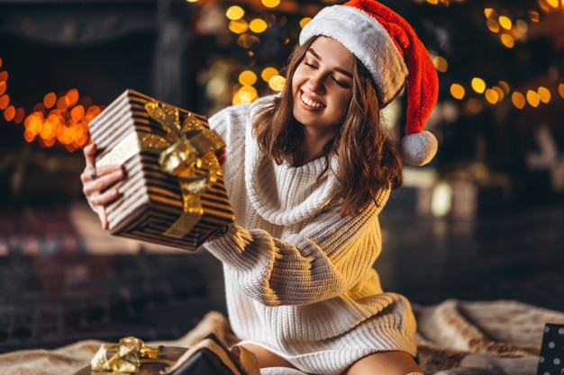 Ładna Kobieta W Ciepłym Swetrze, Skarpetkach I świątecznej Czapce, Siedząca Na Podłodze Premium Zdjęcia