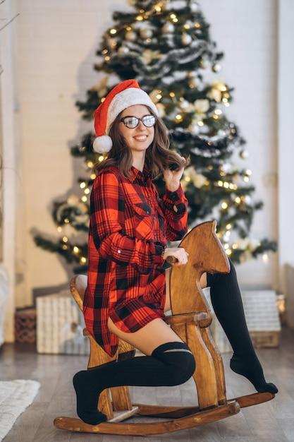 Ładna Kobieta W Koszuli I Skarpetkach Dobrze Się Bawi, Jeżdżąc Na Drewnianej Huśtawce Z Koniem Premium Zdjęcia