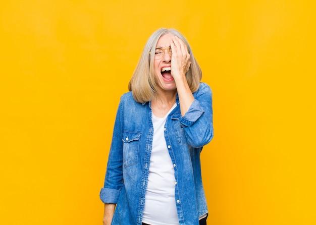 Ładna Kobieta W średnim Lub średnim Wieku, Wyglądająca Na Senną, Znudzoną I Ziewającą, Z Bólem Głowy I Dłonią Pokrywającą Połowę Twarzy Premium Zdjęcia