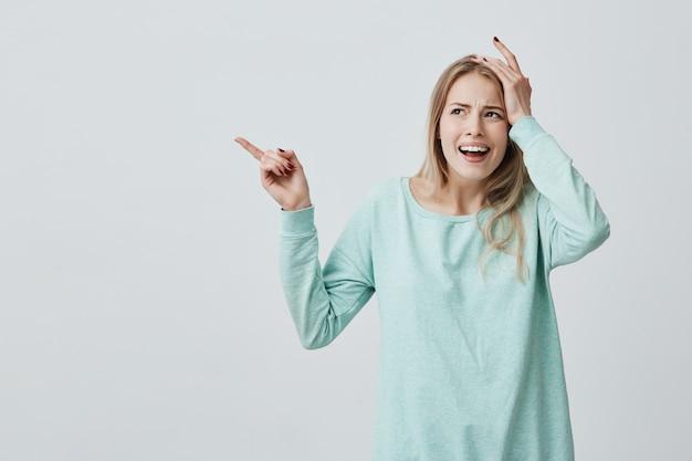 Ładna Kobieta Z Blond Długimi Włosami Trzymająca Rękę Na Głowie, Jakby Zapomniała Czegoś Ważnego, Wskazując Palcem Wskazującym Na Boki Darmowe Zdjęcia