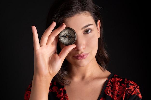 Ładna Kobieta Z Kompasem Zakrywającym Jej Oko Premium Zdjęcia