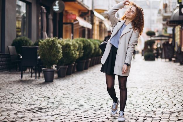 Ładna kobieta z kręconymi włosami, chodzenie na ulicy kawiarni Darmowe Zdjęcia