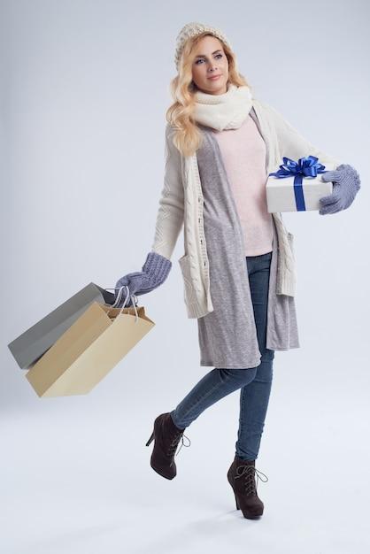 Ładna kobieta z prezentami pozuje przeciw białemu tłu Darmowe Zdjęcia