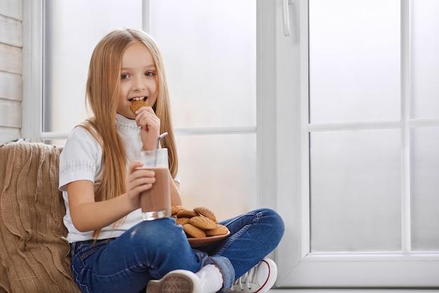 Ładna Mała Dziewczynka Je Ciastka Z Czekoladowym Mlekiem Premium Zdjęcia