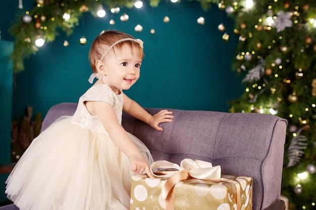 Ładna Mała Dziewczynka W Biel Sukni Bawić Się I Jest Szczęśliwy O Choince I światłach. Premium Zdjęcia