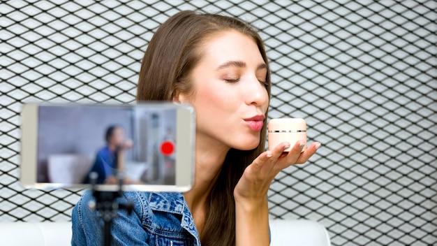 Ładna Młoda Blogerka Prezentuje Kosmetyk Kosmetyczny I Transmituje Wideo Na żywo Do Sieci Społecznościowej Za Pomocą Technologii Smartfonów Premium Zdjęcia