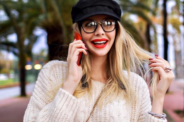 Ładna Młoda Blondynka Rozmawia Przez Telefon, Elegancki Codzienny Strój, Kapelusz, Sweter I Przezroczyste Okulary, Pozytywne Emocje, Palmy Dookoła. Darmowe Zdjęcia