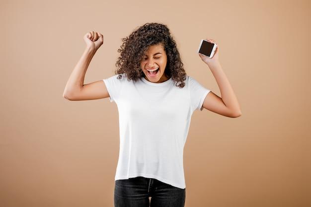 Ładna młoda czarna dziewczyna z telefonem w ręce odizolowywającej nad brązem Premium Zdjęcia