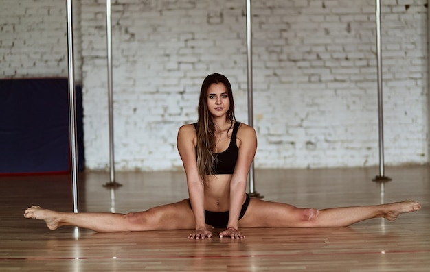 Ładna młoda kobieta robi nogę rozszczepiającemu siedzieć na podłoga Darmowe Zdjęcia