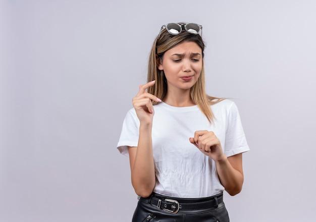 Ładna Młoda Kobieta W Białej Koszulce I Okularach Przeciwsłonecznych, Próbuje Przypomnieć Sobie Coś Na Białej ścianie Darmowe Zdjęcia