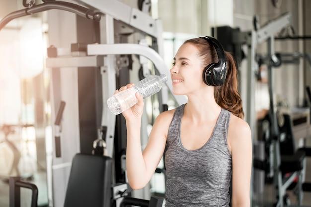 Ładna młoda sport kobieta jest wodą pitną w gym Premium Zdjęcia
