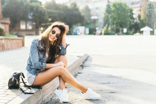 Ładna Młoda Uśmiechnięta Brunetki Dziewczyny Relaksować Plenerowy Na Ulicie. Premium Zdjęcia