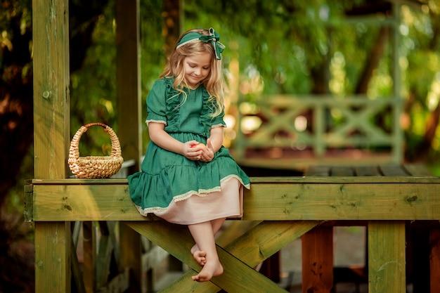 Ładna Piękna Dziewczyna O Blond Włosach W Zielonej Rustykalnej Sukni Siedzi W Pobliżu Wiklinowego Kosza Na Drewnianej Altanie W Lecie Boso. Premium Zdjęcia