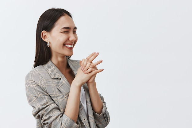 Ładna Radosna Kobieta śmiejąca Się Z Radości I Entuzjazmu, Stojąca Na Wpół Odwrócona Nad Szarą ścianą, ściskająca Dłonie, Patrząc W Prawo Darmowe Zdjęcia