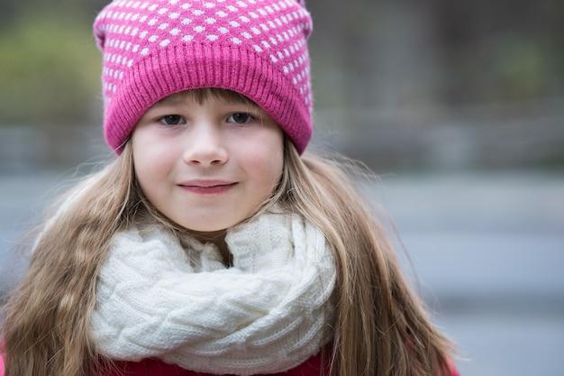 Ładne Dziecko Dziewczyna W Ciepłe Zimowe Ubrania Z Dzianiny Na Zewnątrz. Premium Zdjęcia